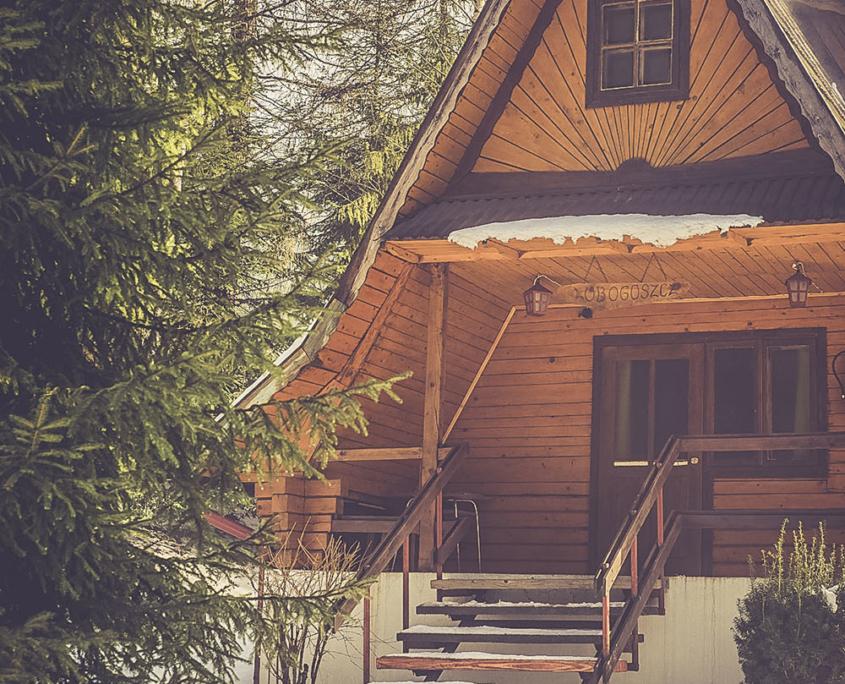 Ośrodek nad Potokiem, zaśnieżony drewniany domek na terenie ośrodka
